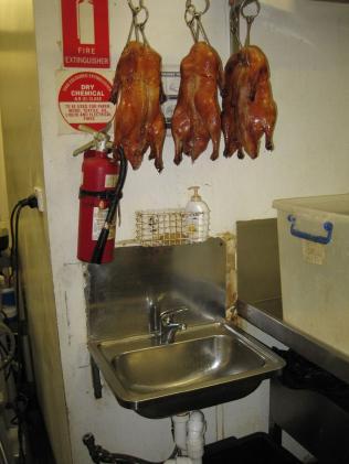 เป็ดย่างรอเสิร์ฟลูกค้าถูกแขวนอยู่เหนืออ่างล้างมือที่สกปรก (ภาพจากเทศบาลเขต Brisbane City)