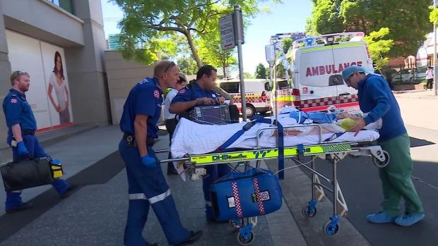 คนไข้หญิงกำลังถูกลำเลียงออกจากคลีนิคสาขา Bondi ไปส่งยังโรงพยาบาล St Vincent's (ภาพชั่วคราวจากนสพ. SMH)(