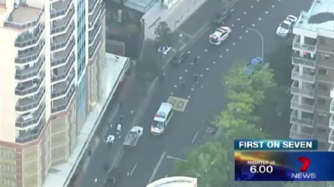ถนน Charles St. หน้าสำนักงานใหญ่ตำรวจรัฐน.ซ.ว. จะเห็นศพของผู้สังหาร และเหยื่อคลุมด้วยผ้าสีขาว : ภาพจากทีวี 7 News