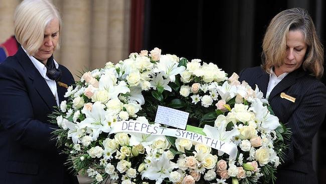 สตรีสองคนถือหรีดของนาย Luke Mitchell พลเมืองดีที่ถูกนักศึกษาไทยแทงเสียชีวิต : ภาพจากสำนักข่าว SBS ต้นฉบับ AAP