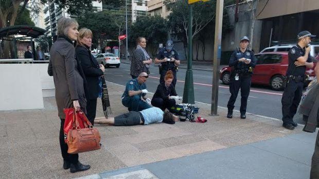 ทีมแพทย์และพยาบาลจากหน่วยแพทย์เคลื่อนกำลังปฐมพยาบาลนาย Mark McGrice ที่ถนน Ann St. ก่อนรีบนำส่งโรงพยาบาล : ภาพชั่วคราวจากนสพ. Brisbane Time