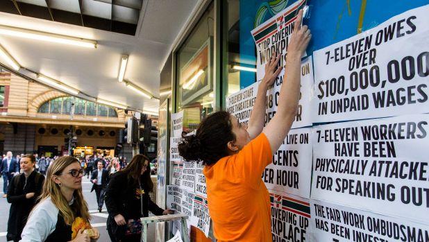 กลุ่มผู้ประท้วงปิดป้ายต่อต้านร้านสะดวกซื้อ 7-Eleven ในใจกลางนครเมลเบิร์น : ภาพจากนสพ. the Age