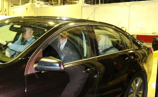 ภาพผู้ต้องหาชายวัย 68 ปีมีผ้าคลุมศีรษะนั่งอยู่เบาะท้ายรถ ขณะตำรวจนำตัวออกจากวอทช์เฮาส์ในคืนวันที่ 28 ก.ย.