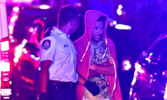 นาย Abdul Barati พูดคุยกับตำรวจในระหว่างที่พนักงานดับเพลิงกำลังดับไฟไหม้บ้าน : ภาพชั่วคราวจากนสพ. Telegraph