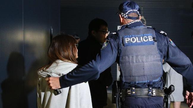 แรงงานต่างชาติขณะถูกตำรวจนำตัวออกจากฟาร์มไปยังนครบริสเบน : ภาพชั่วคราวจากนสพ. The Courier Mail
